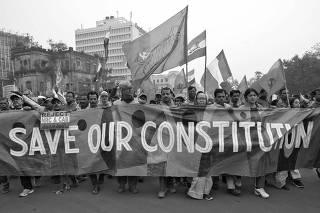 Demonstrators carry a banner and flags as they attend a protest rally against the National Register of Citizens and a new citizenship law, in Kolkata