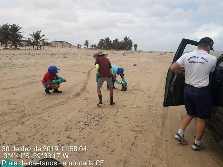 Voluntários e Marinha limpam praia atingida por óleo no Ceará