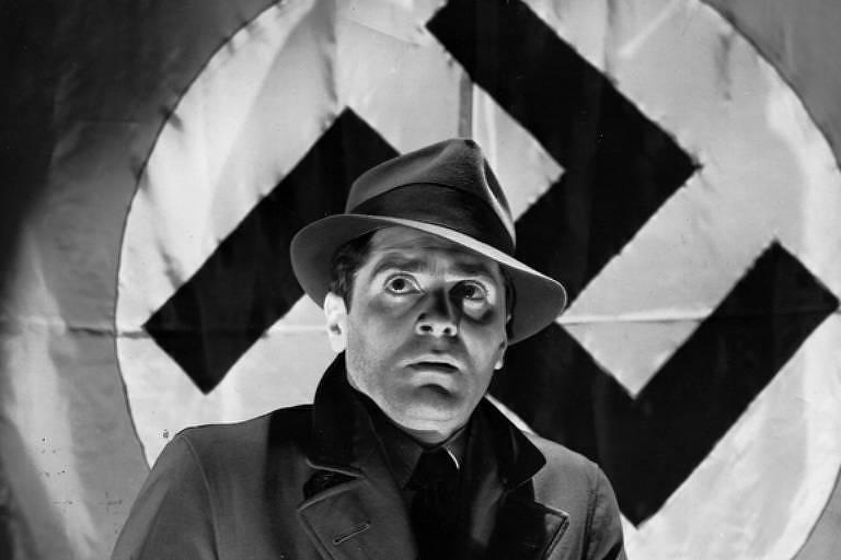 Homem de chapéu e casaco diante de uma bandeira nazista