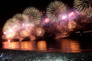 People watch as fireworks explode over Copacabana beach during New Year celebrations in Rio de Janeiro