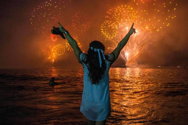 Com a água do mar até os joelhos, mulher de costas e vestida de branco ergue braços