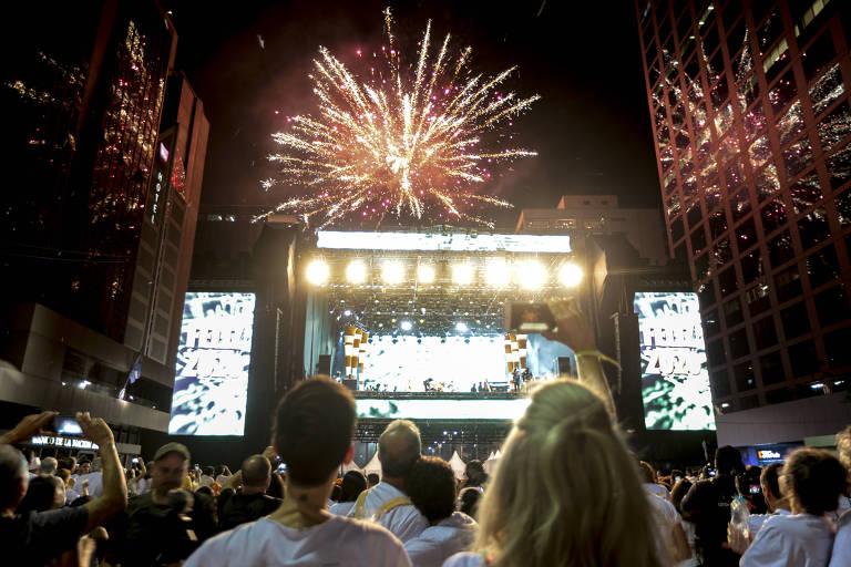 Fogos de artifício sobre palco refletem em prédios