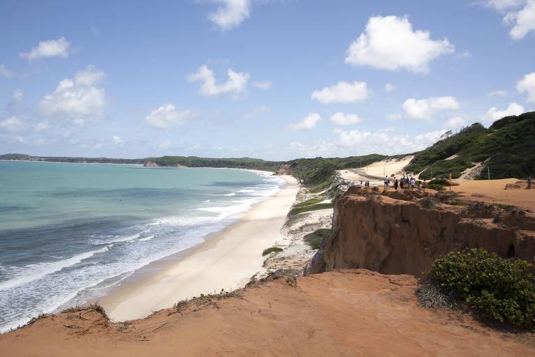 Praia em baía com falésia avermelhada no primeiro plano e dunas com vegetação