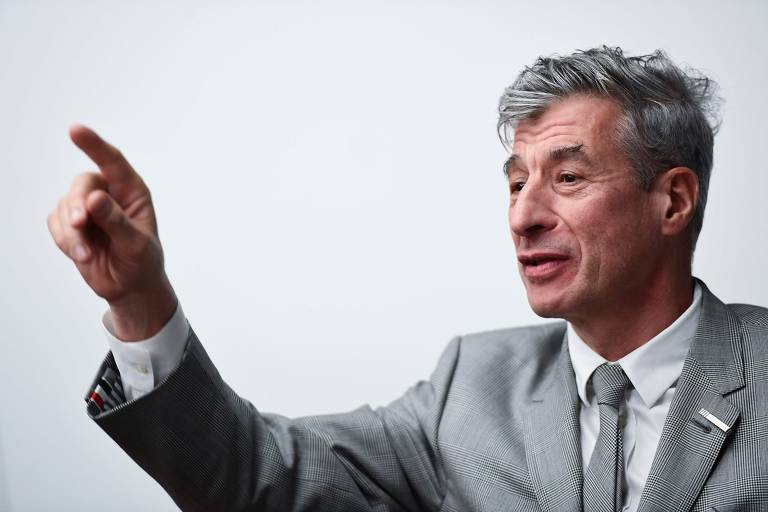 O artista italiano Maurizio Cattelan, em Milão; na foto vemos apenas o artista, que é um homem magro e grisalho, com o cabelo cortado curto, vestindo terno e gravata em tons de cinza; ele está apontando para algo fora do quadro com seu indicador direito