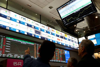 FILE PHOTO: People are seen in front of an electronic board showing the graph of the recent fluctuations of market indices on the floor of Brazil's B3 Stock Exchange in Sao Paulo