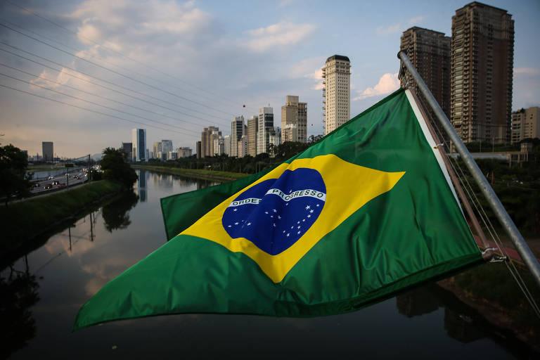 Vista de prédios de alto padrão na marginal Pinheiros, com bandeira do Brasil à frente pendurada na ponte Cidade Jardim