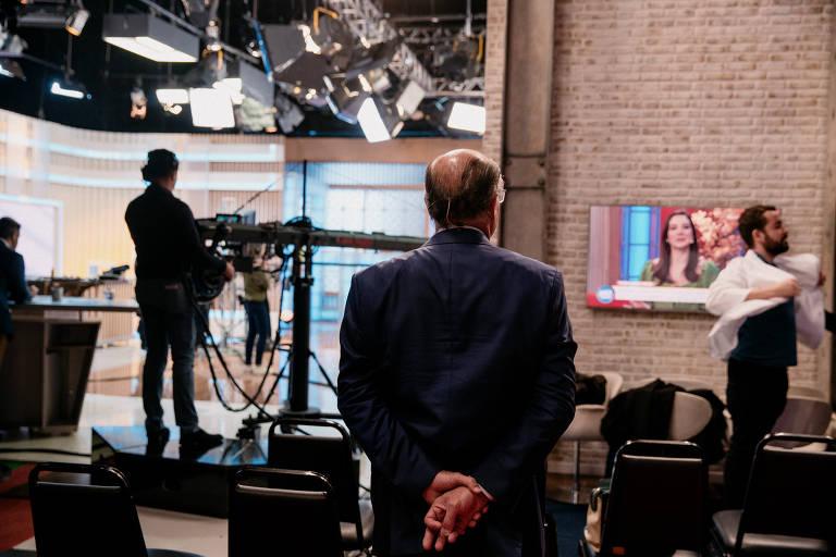Geraldo Alckmin observa gravação do programa Aqui na Band; ele participa da atração matinal da TV Bandeirantes desde novembro; na foto, ele está de costas; à sua esquerda, ao fundo, vê-se um técnico e, à direita, na direção para a qual olha o político, um monitor mostra o que acontece na transmissão
