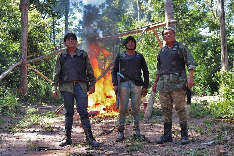 """Laércio Guajajara, Paulo Paulino Guajajara e Olímpio Guajajara, membros do grupo """"Guardiões da Floresta"""", retratados em abril de 2019, na Terra Indígena Arariboia, no Maranhão; em novembro, Laércio foi ferido no atentado que matou Paulino, o Lobo Mau, que tinha 26 anos; ao fundo, atrás do trio que usa roupas de andar na selva e coletes à prova de balas, vê-se uma fogueira em meio a árvores"""