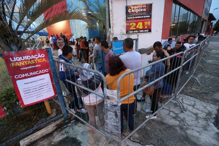 Consumidores fazem fila para buscar descontos em liquidação anual