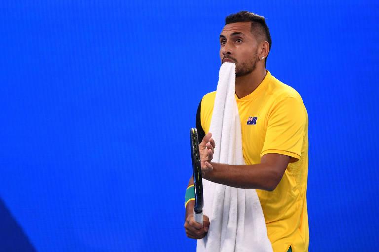 Kyrgios bate em sua raquete com uma toalha na boca
