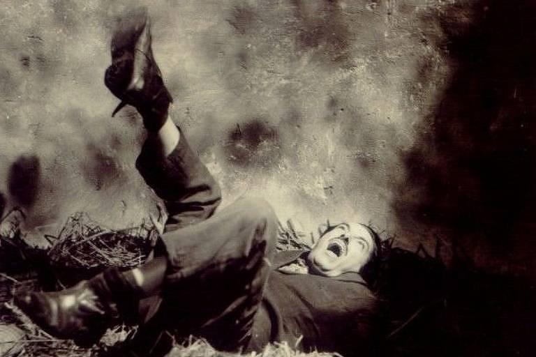Homem de terno deitado na grama com os pés em movimento e gritando
