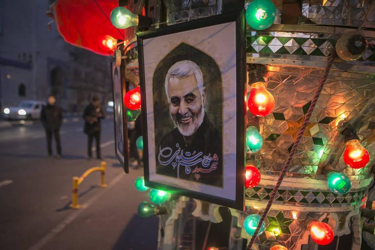 Pôster com o rosto de Qassim Suleimani em rua de Teerã entre luzes coloridas