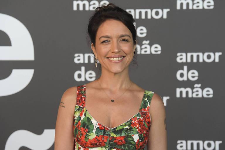 Manuela Dias, autora de novelas, veste vestido colorido e sorri para foto