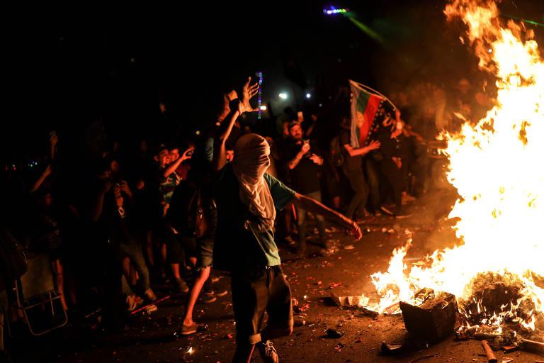 Manifestante atira objeto em fogueira na praça Baquedano durante a virada do Ano em mais um protesto contra o governo, em Santiago