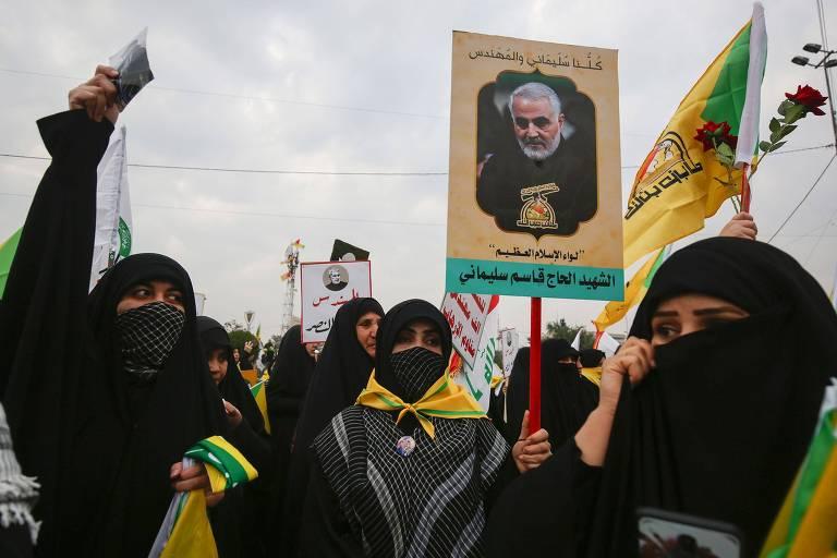 Mulheres de jihab  protestam e seguram cartaz com foto do general falecido