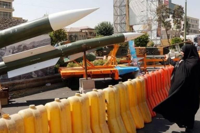 Foto demonstra mísseis em exibição. Do lado direito, uma mulher, trajando roupa preta que deixa apenas seu rosto visível, fotografa os mísseis