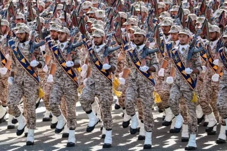 militares marcham em parada, trajam uniforme camuflado na cor  terrosa e calçados brancos com a sola preta