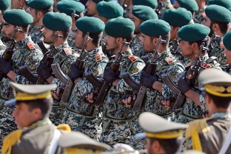 militares estão em filas, trajam uniforme camuflado e boina verde, olham para a esquerda