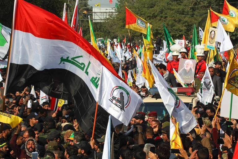 Com bandeiras de milícia pró-Irã, manifestantes participam do ato em homenagem aos mortos em Bagdá