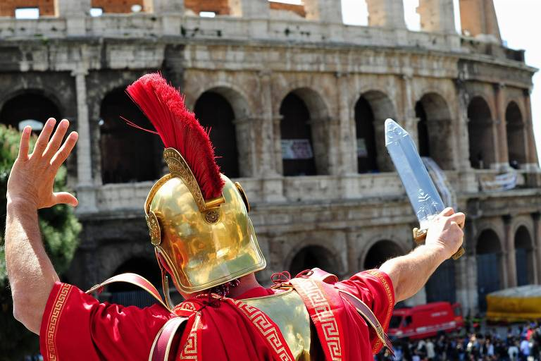 Homem vestido de gladiador, para posar em fotos com turistas, em frente ao Coliseu, em Roma