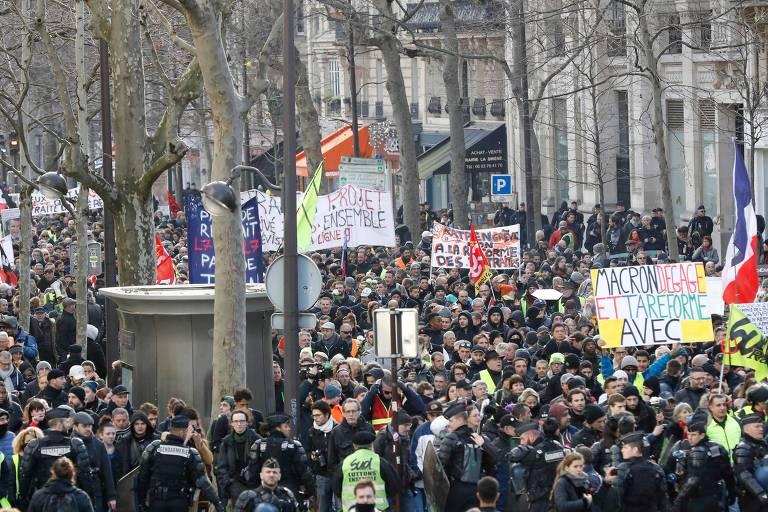 Manifestantes em rua com placas e bandeiras francesas
