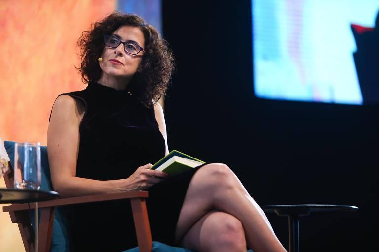 Mulher de vestido preto e óculos sentada seguro livro semi-aberto