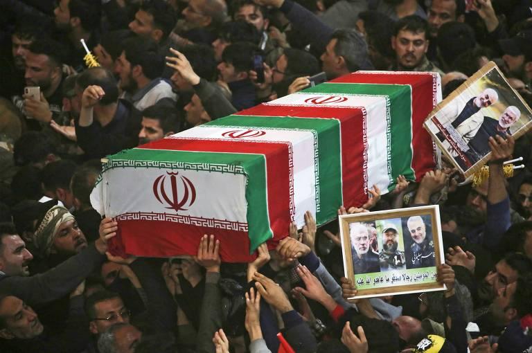 Multidão carrega caixão com as mãos e exibe cartazes de general com barba e cabelos grisalhos durante cortejo fúnebre. Caixão é coberto pela bandeira do Irã