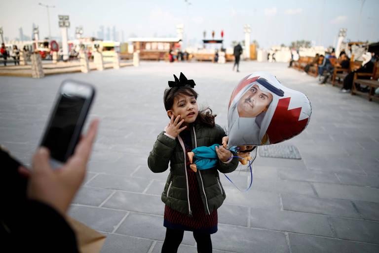 Criança posa para foto segurando balão com a imagem do emir do Qatar