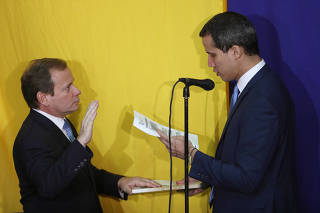Venezuelan opposition lawmaker Juan Pablo Guanipa swears-in in front of opposition leader Juan Guaido, after being elected as the first vice-president of the National Assembly by Venezuelan opposition legislators, in Caracas