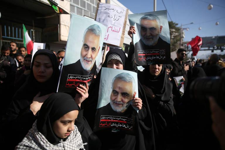 Um grupo de mulheres vestindo roupas pretas segura cartazes mostrando o rosto de general iraniano morto, diante de bandeiras e de um céu azulado