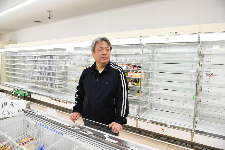 Retrato de Mitoshi Matsumoto em sua loja de conveniência; atrás, as prateleiras estão vazias