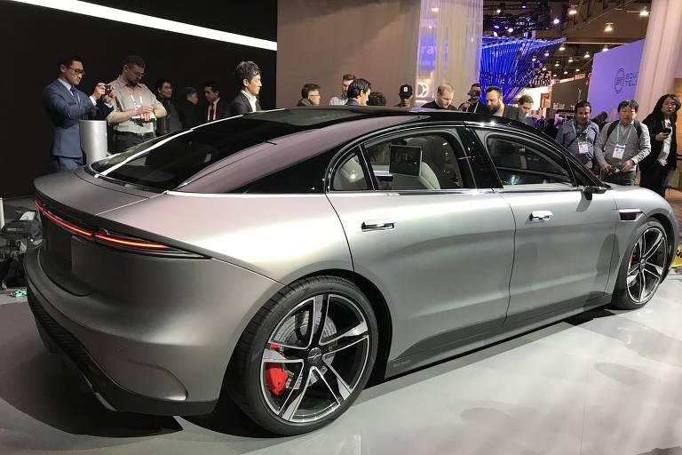 Retrato de um carro cinza claro com parte superior em preto. O tamanho do carro é modelo sedã, com quatro portas, e tem design futurista