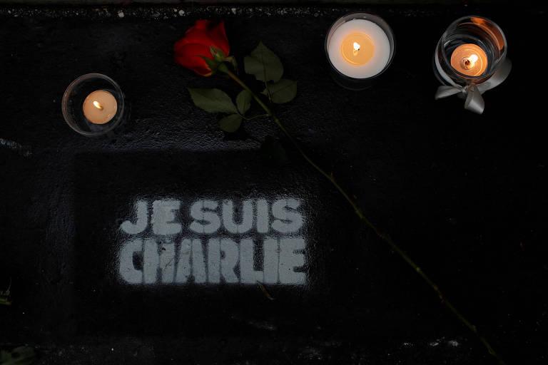 Flores e velas colocadas do lado de fora da antiga sede do jornal Charlie Hebdo, em Paris