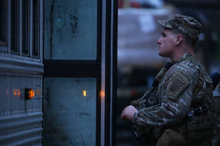 A soldier boards a bus in preparation for deployment to the Middle East, at Fort Bragg in Fayetteville, N.C., on Jan. 4, 2020. (Travis Dove/The New York Times)