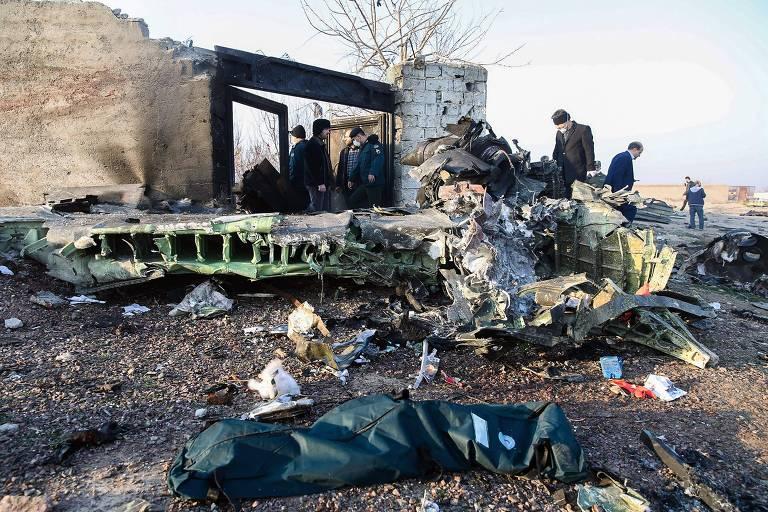 Pessoas observam destroços após queda de avião ucraniano no Irã