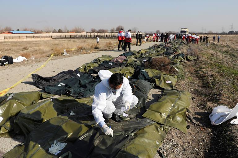 Corpos de passageiros são colocados em sacos para transporte