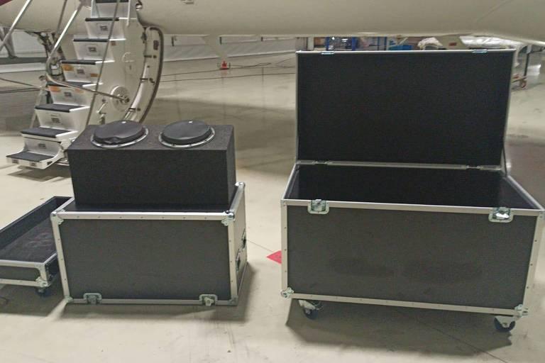 A foto mostra duas caixas pretas de rodinhas abertas em primeiro plano. Ao fundo, a escada de um avião.