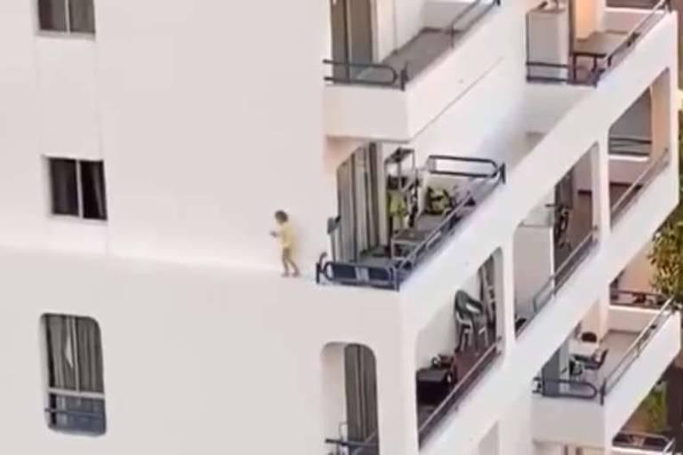 Criança anda no parapeito de janela de prédio