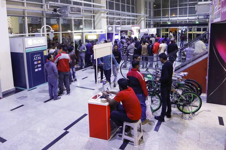 Imigrantes fazem filas em frente aos caixas eletrônicos do shopping em Asian Town