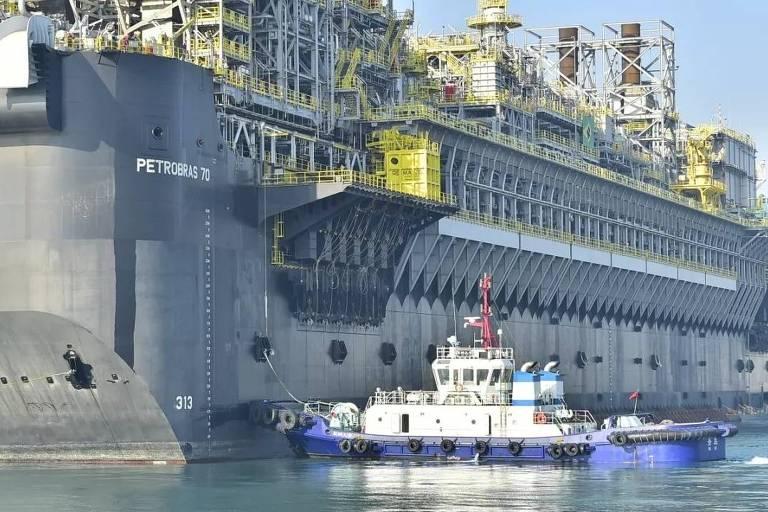 Retrato de um plataforma de petróleo; ao lado da embarcação está um barco menor