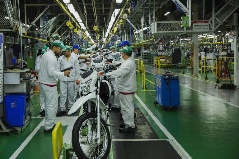 Retrato de um interior de uma fábrica de motos; quatro homens, que vestem roupa branca e equipamentos de segurança do trabalho, estão em volta de uma motocicleta