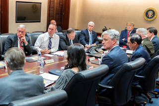 U.S. President Donald Trump and Vice President Mike Pence speak with senior White House advisors during a meeting about Iran missile attack on U.S. military facilities in Iraq, in the Situation Room of the White House, Washington