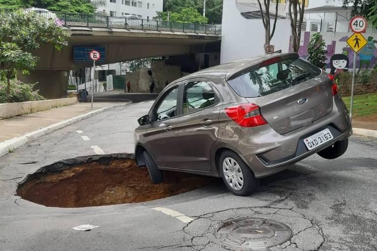Carro é engolido por cratera formada na rua Carlos Comenale, na região da Av. Paulista, no acesso para a Avenida Nove de Julho após chuva