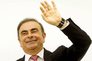 Former Nissan chairman Carlos Ghosn gestures as he finishes his news conference at the Lebanese Press Syndicate in Beirut