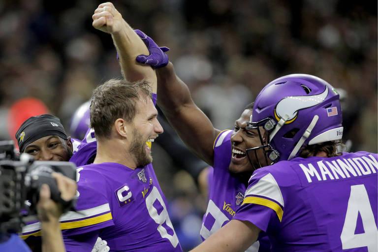 O quarterback Kirk Cousins (à esq.) comemora com companheiros de Vikings a vitória sobre o Saints