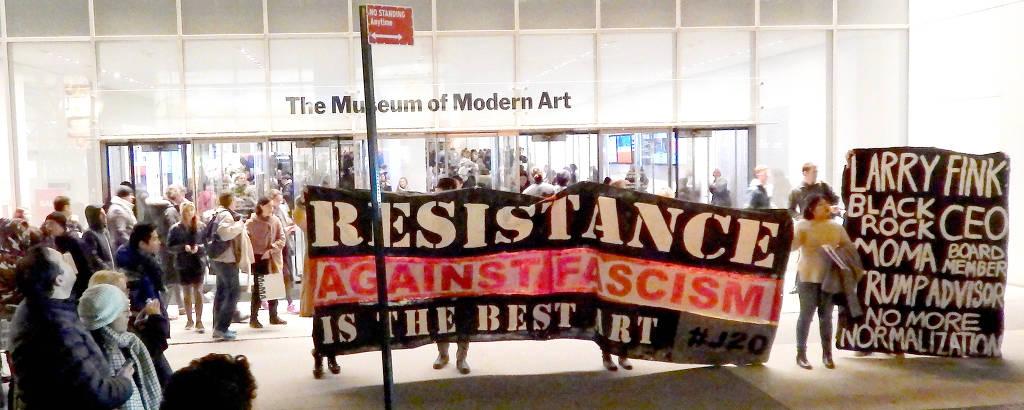 Grupo protesta em frente ao MoMA, em 17 de fevereiro de 2017, pedindo a saída do bilionário Larry Fink do conselho do museu; na grande faixa, levada por quatro pessoas, das quais só se veem os pés, lê-se