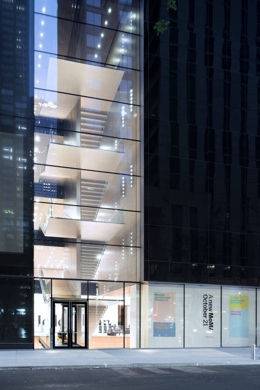 Vista do exterior do MoMA a partir da rua 53; na foto vertical vê-se o contraste entre a escadaria, que é toda transparente e voltada para a rua, e os vidros escuros que compõem o resto da fachada