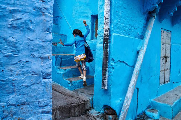 Menina sobre escada em Jodhpur, na Índia