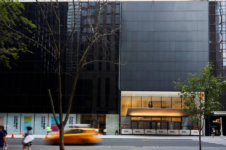 A entrada principal do MoMA (Museu de Arte Moderna de Nova York), na rua 53 Oeste; 15 anos após reforma anterior, prédio foi ampliado e renovado em obra bilionária; a fachada é sóbria, de vidro negro e superfícies metálicas; à esquerda da foto vê-se um táxi amarelo meio fora de foco pela velocidade, e uma árvore magra e solitária
