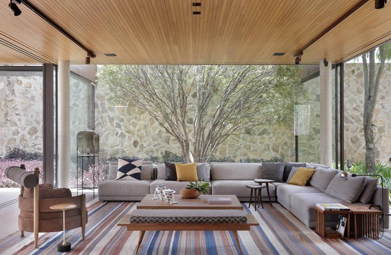 Sala com paredes de vidros e uma árvore